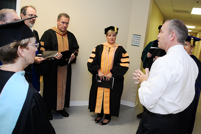 Dr. Dub Oliver chats with colleagues prior to Summer Commencement.