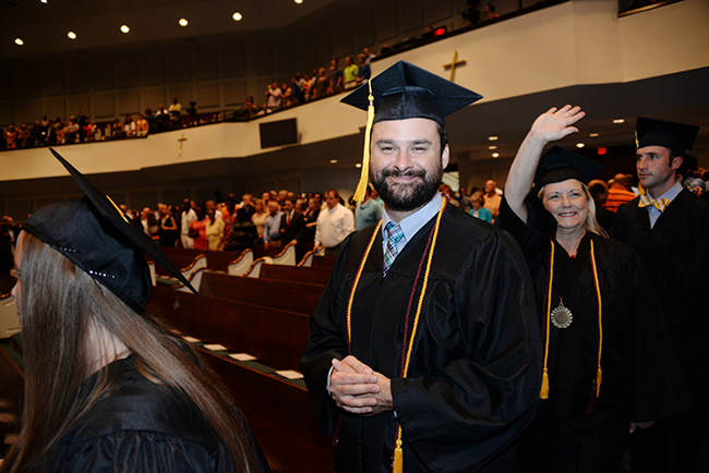 Ben Williams files in with fellow graduates at Summer Commencement.