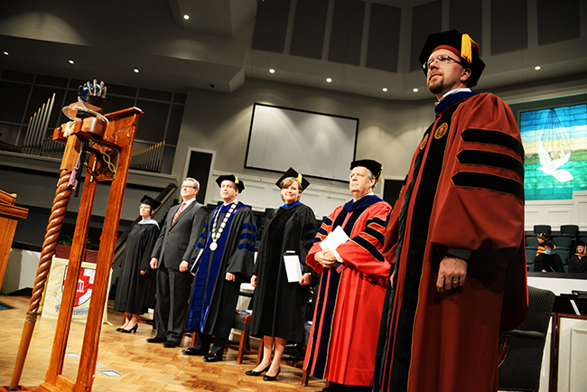 As graduates file in, Justin Barnard, faculty member of the year, stands next to his colleagues and speakers at Summer commencement.