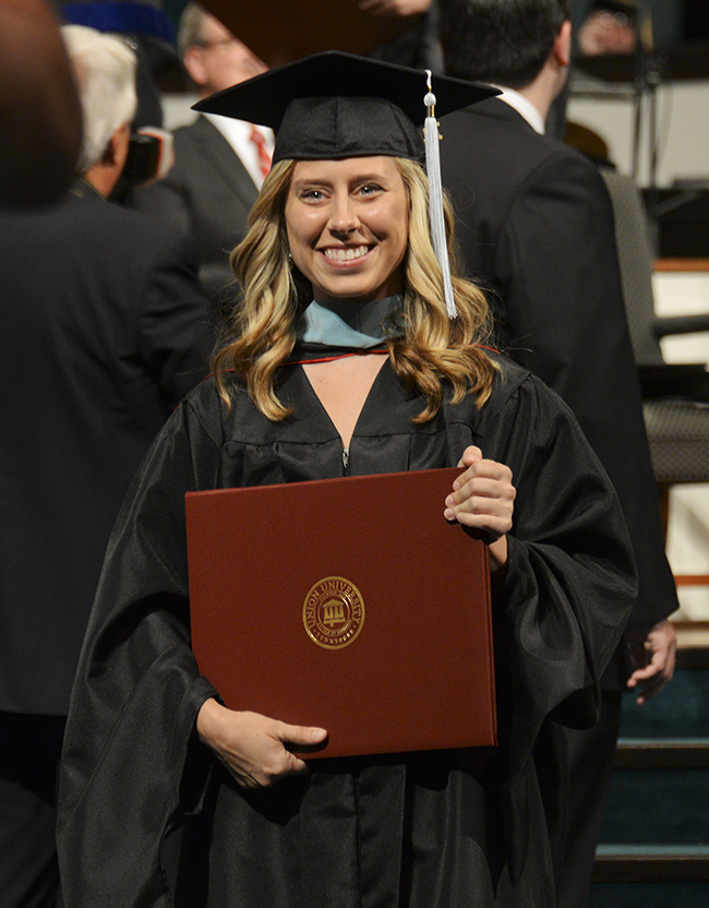 A graduate proudly displays her diploma for nearby family members.