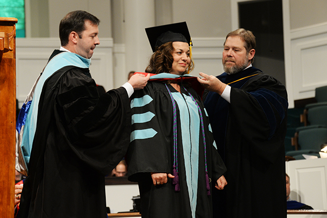 A doctoral graduate receives her hood at Summer graduation.
