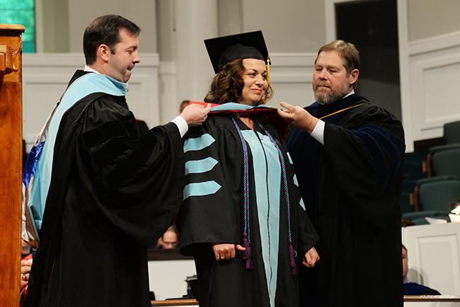 A doctoral graduate receives her hood at Summer graduation.