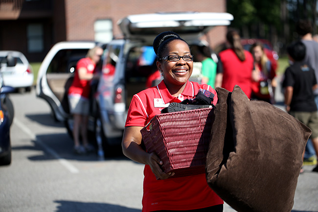 Renee Jones carries a box for a new student
