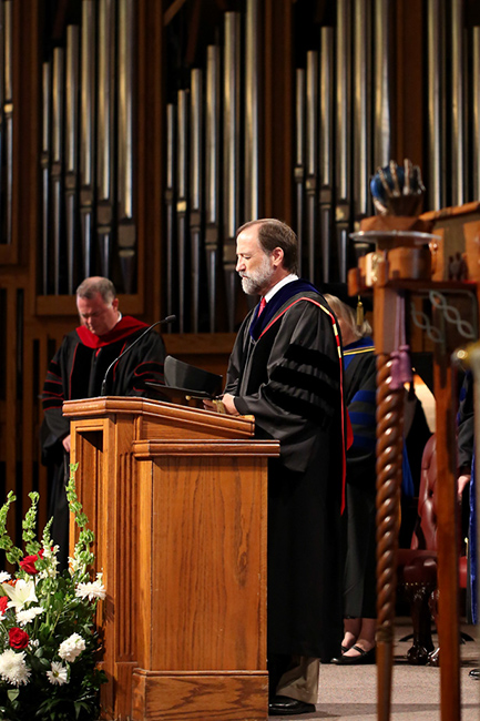 Dr. Poe, faculty member of the year, prays during Convocation.
