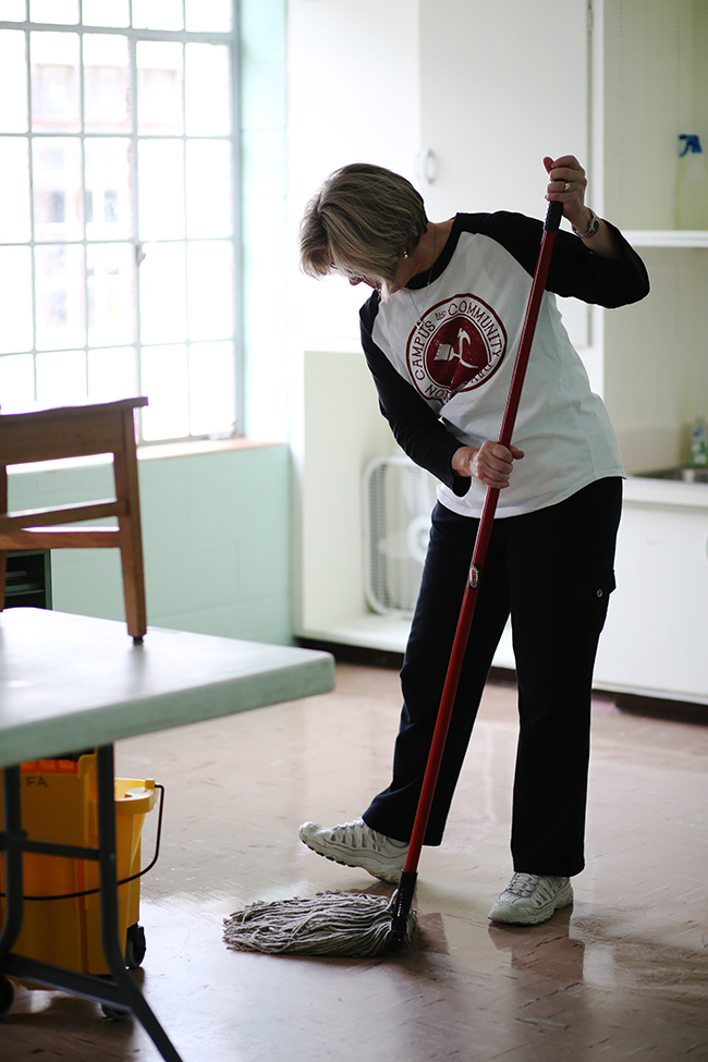 Tina Netland mops the floor during a service project
