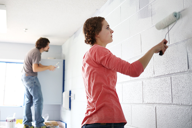 A group from the university paints a room at ROAR, an after school program