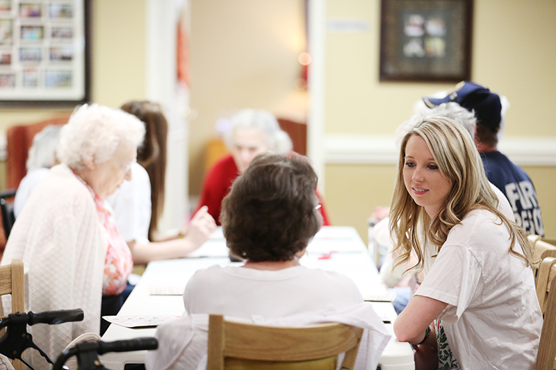 Members of Chi Omega chat with residents of Recency Retirement Village during a game of bingo.