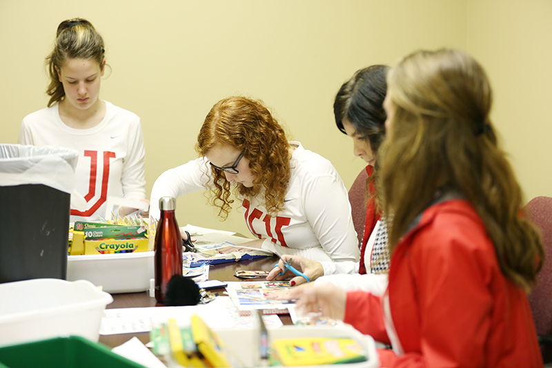 Member of the cheer squad work on preparing art therapy materials at The Star Center