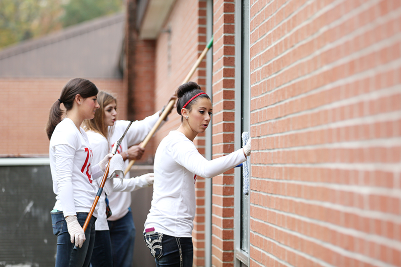 Members of the cheer squad wash windows at The Star Center.