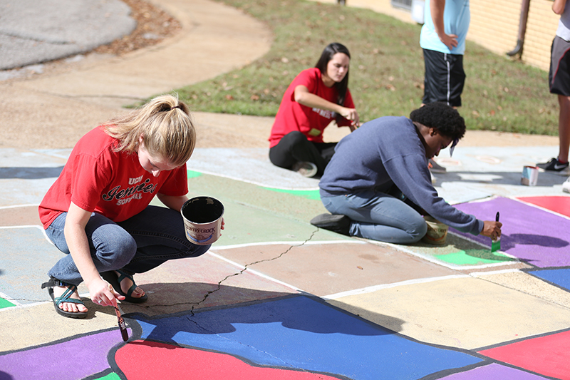 A team of students led by the golf team refreshes a US map on the sidewalk outside of Alexander Elementary.